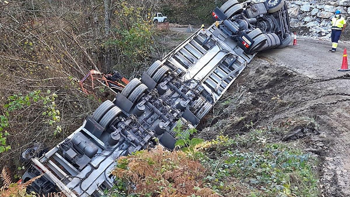 El camión, volcado en la obra de la carretera.