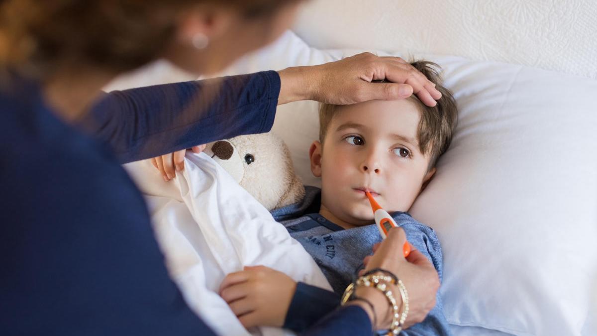 Una mujer toma la temperatura a su hijo enfermo.