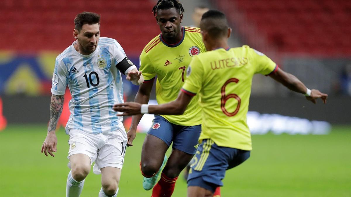 Messi conduce el balón ante dos jugadores de Colombia.