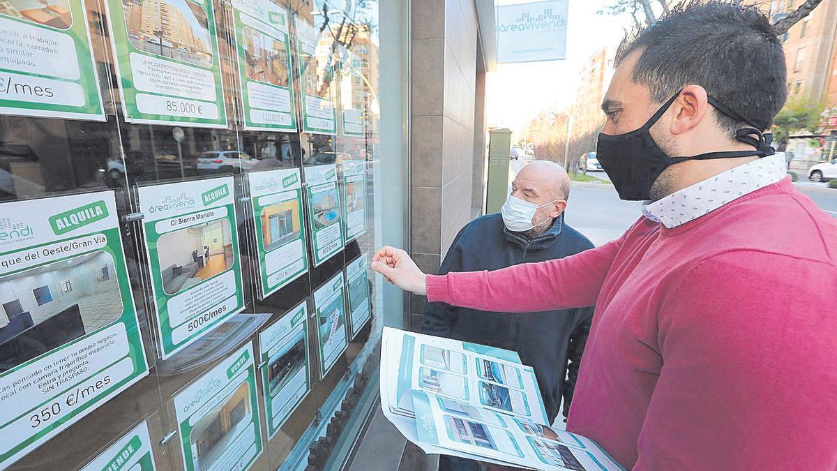 Un agente inmobiliario enseña carteles de viviendas en venta o alquiler en Castellón