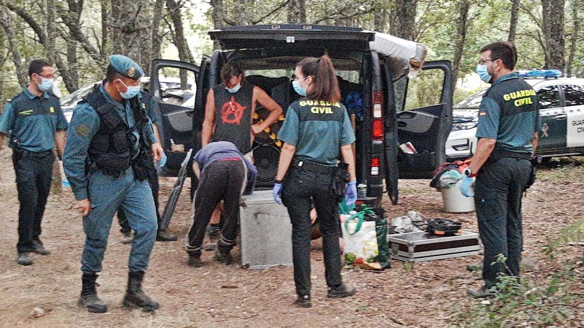 Agentes de la Guardia Civil siguen de cerca la recogida de material para meterlo en el coche de unos jóvenes acampados en  Vime. | A. S