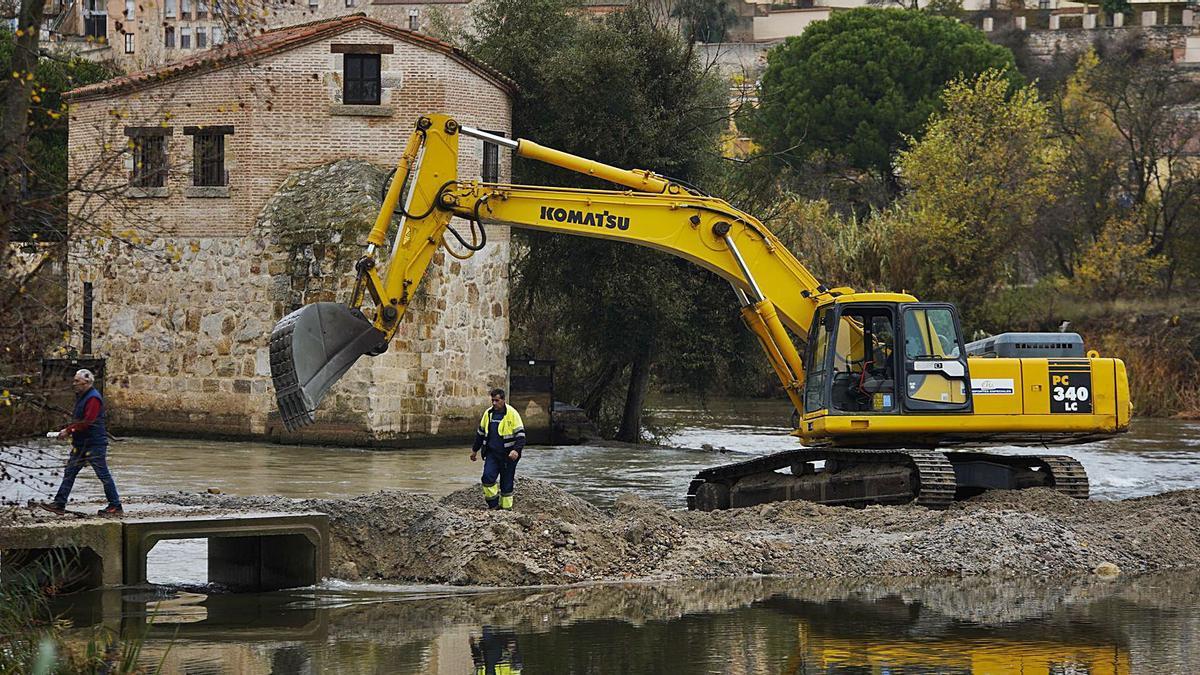 La arena del propio río sirve para construir el pequeño dique que contendrá el paso del agua en la zona.   Jose Luis Fernández