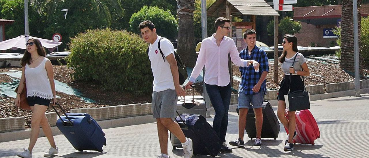 Varios jóvenes cargan con maletas a las puertas de la estación de tren de Gandia.   XIMO FERRI