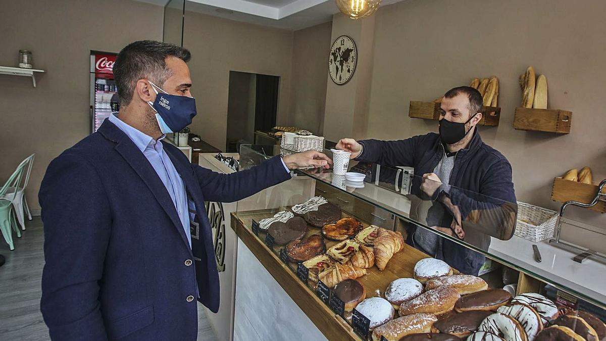Abajo, un hombre se lleva un café en Alicante.