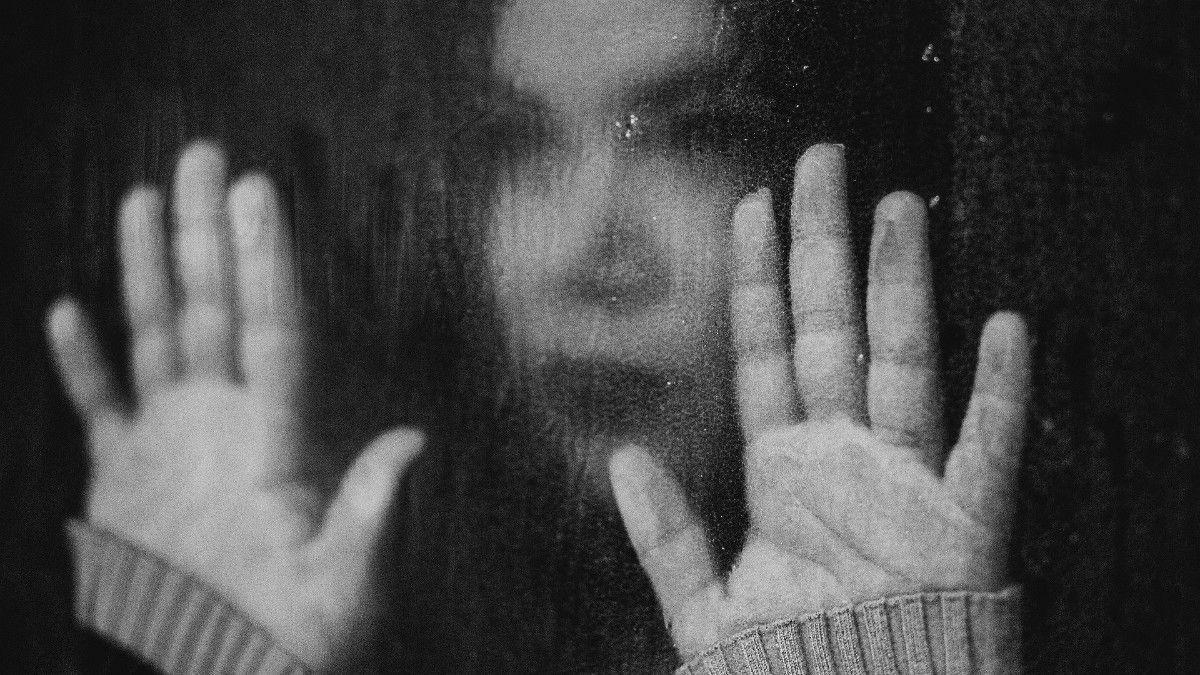 Una joven tras una ventana