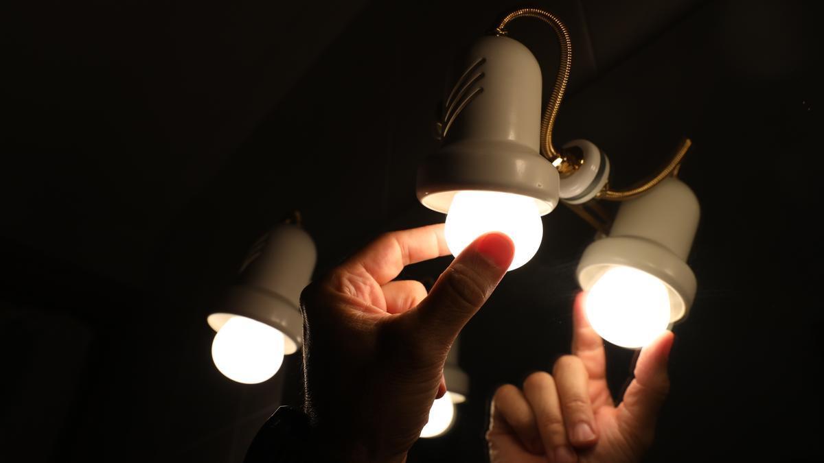 Una persona cambia la bombilla de una lámpara.