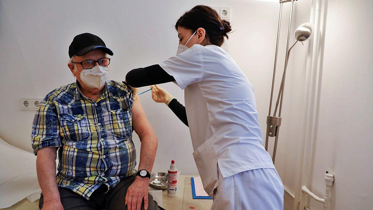 Una sanitaria administra ayer en Berlín a una persona mayor una vacuna contra la covid. |  REUTERS/ALESSIA COCCA