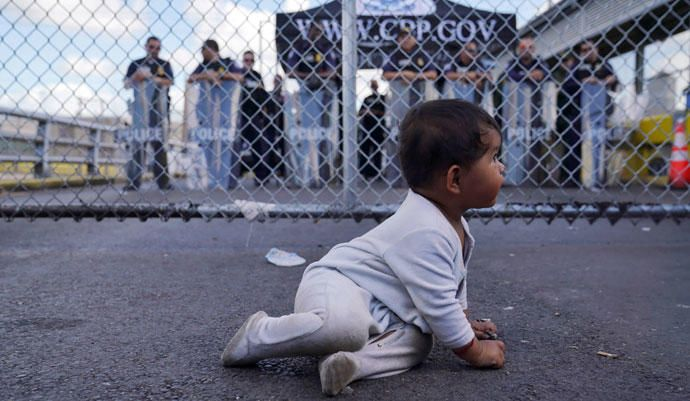 Un bebé se sienta frente a los funcionarios de Aduanas y Protección Fronteriza de EEUU