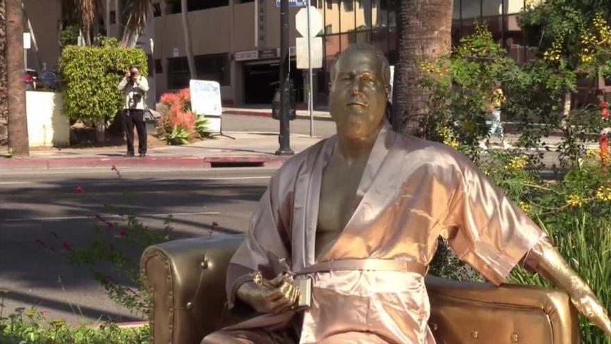 Dos artistas plantan una estatua dorada de Harvey Weinstein con el batín abierto