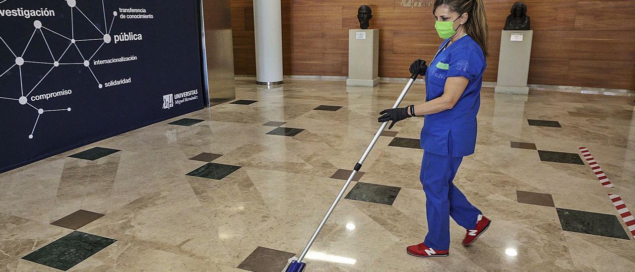 Una mujer limpia las instalaciones del edificio Rectorado y Consejo Social de la Universidad Miguel Hernández. | ANTONIO AMORÓS