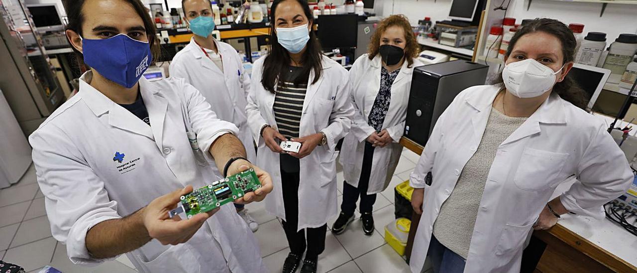 Sobre estas líneas, por la izquierda, José Francisco Beltrán, Andrea González, Teresa F. Abedul, María Dolores Cima y Estefanía Costa, ayer en el laboratorio. A la derecha, González con el detector. | L. Murias