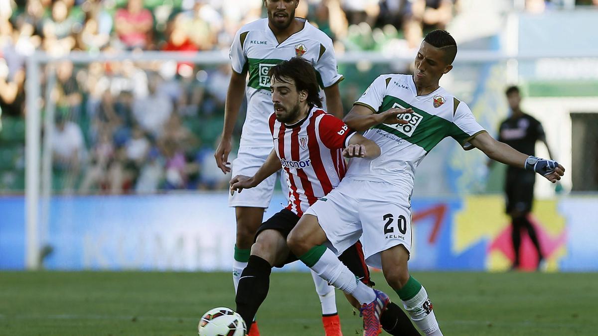 Beñat intenta colarse entre los jugadores del Elche Jonathas y Fayçal Fajr en 2015.