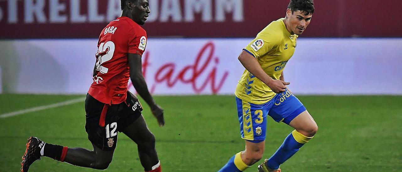 Sergio Ruiz, centrocampista de la UD Las Palmas, conduce el balón mientras es perseguido por Baba, mediocentro del Mallorca.