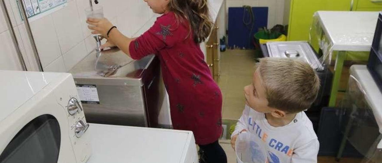 Dos niños cogen agua en el surtidor de agua de un colegio. // Alba Villar