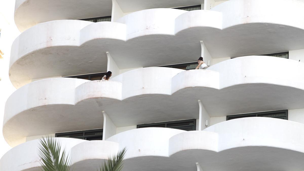 Dos jóvenes en un balcón del hotel Palma Bellver, donde estaban confinados los estudiantes.