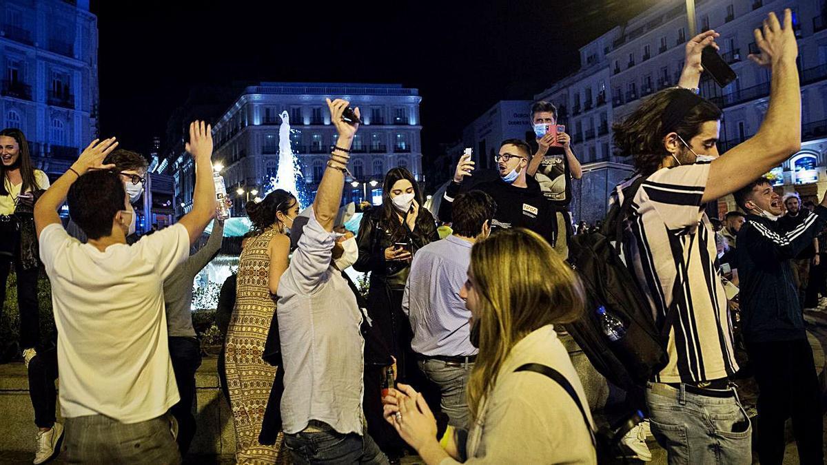 Varias personas festejando ayer en la Puerta del Sol de Madrid, tras el fin del estado de alarma. | LUCA.P/EFE
