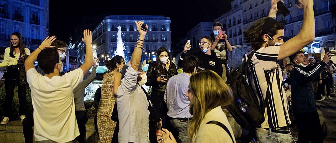 Varias personas festejando en la Puerta del Sol de Madrid, tras el fin del estado de alarma.