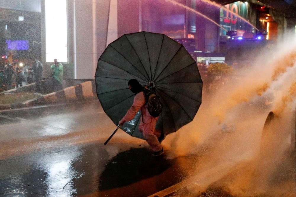 A man takes cover behind an umbrella during an ...