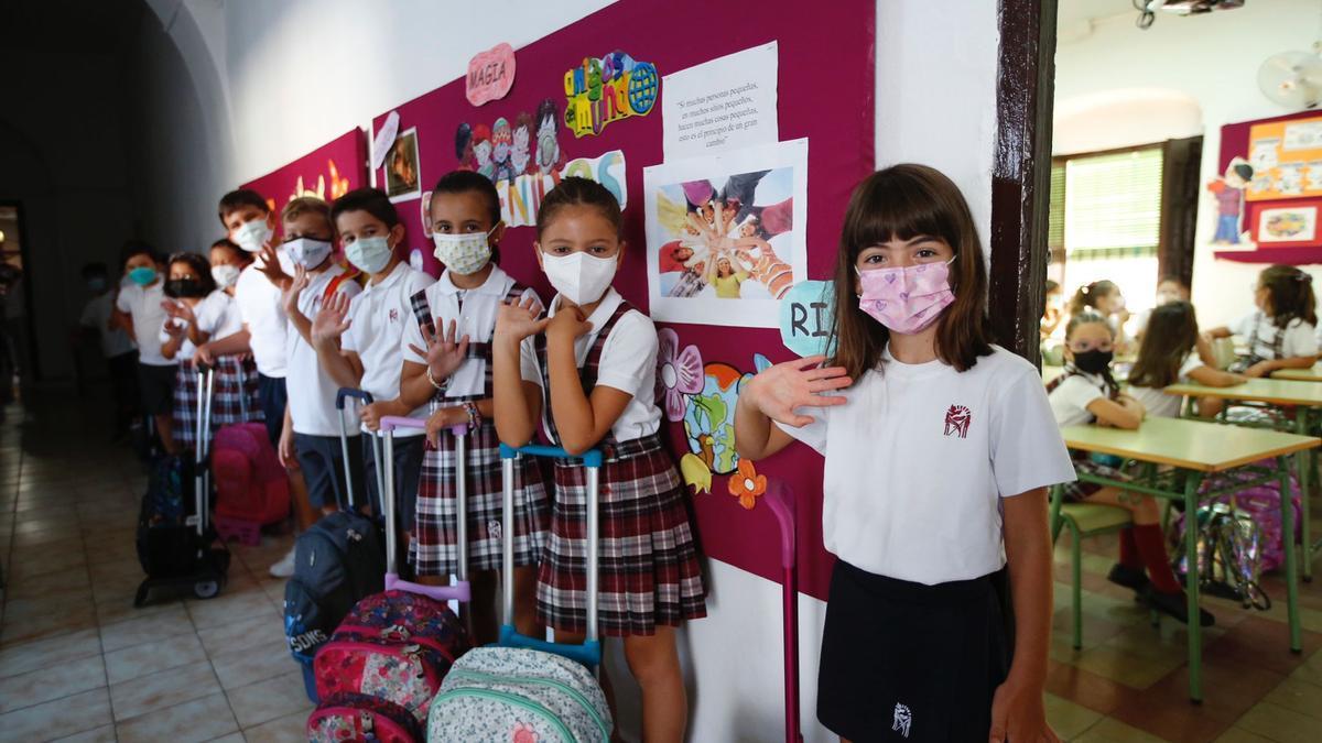 Niñas y niños saludan antes de entrar a clase, este viernes 10 de septiembre, primer día de la vuelta al cole.