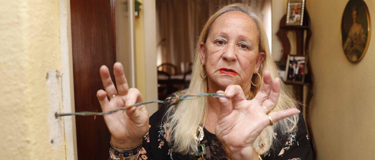 Sara Guntín enseña el cable de su telefonillo, que se lo quemaron.