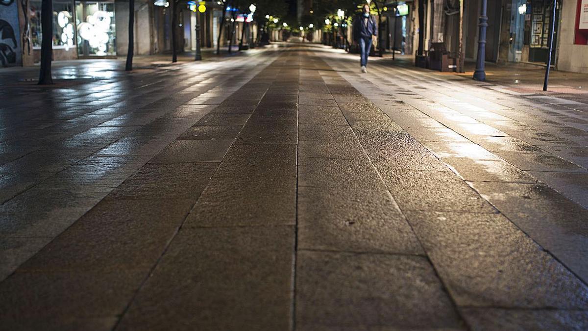 Una persona camina por la calle Paseo en la segunda noche del toque de queda en Ourense.  | // BRAIS LORENZO