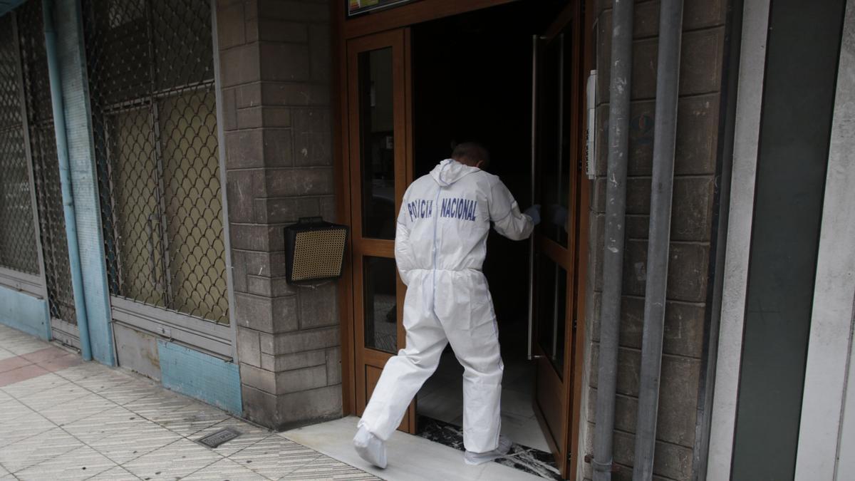 Un policía de la Científica en el portal del bloque de viviendas donde sucedieron los hechos.