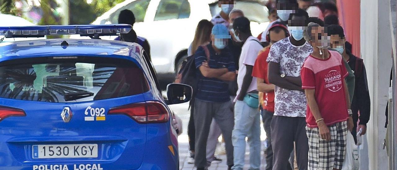 Cola de personas que esperan en la calle para acceder al comedor de Cáritas. |