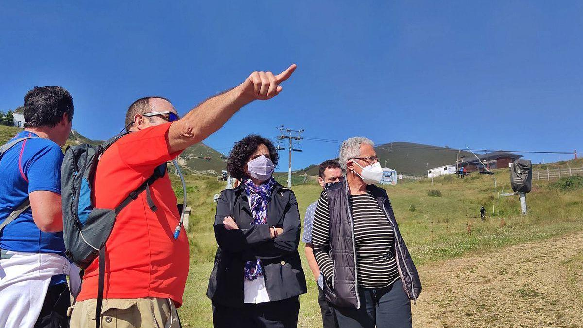 Berta Piñán conversa con senderistas junto a Loli Martínez, portavoz del PSOE de Lena, con el remonte del Brañillín funcionando detrás.