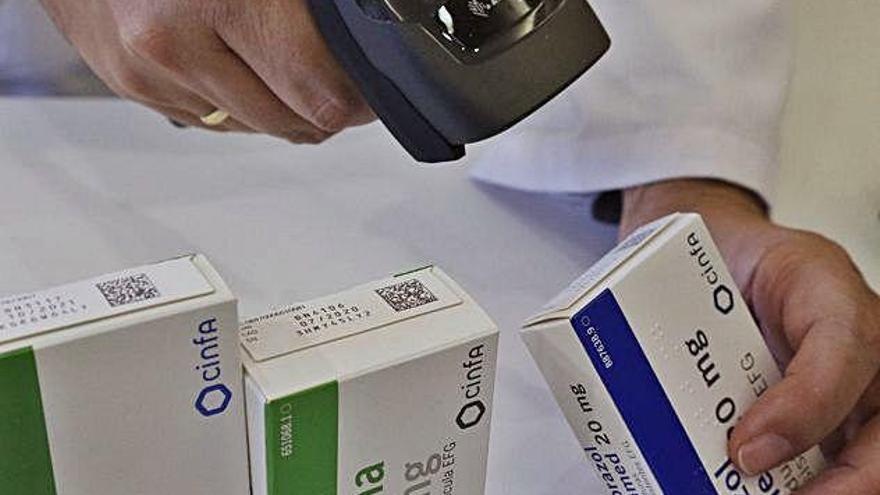 Un farmacéutico escanea el código de un medicamento.