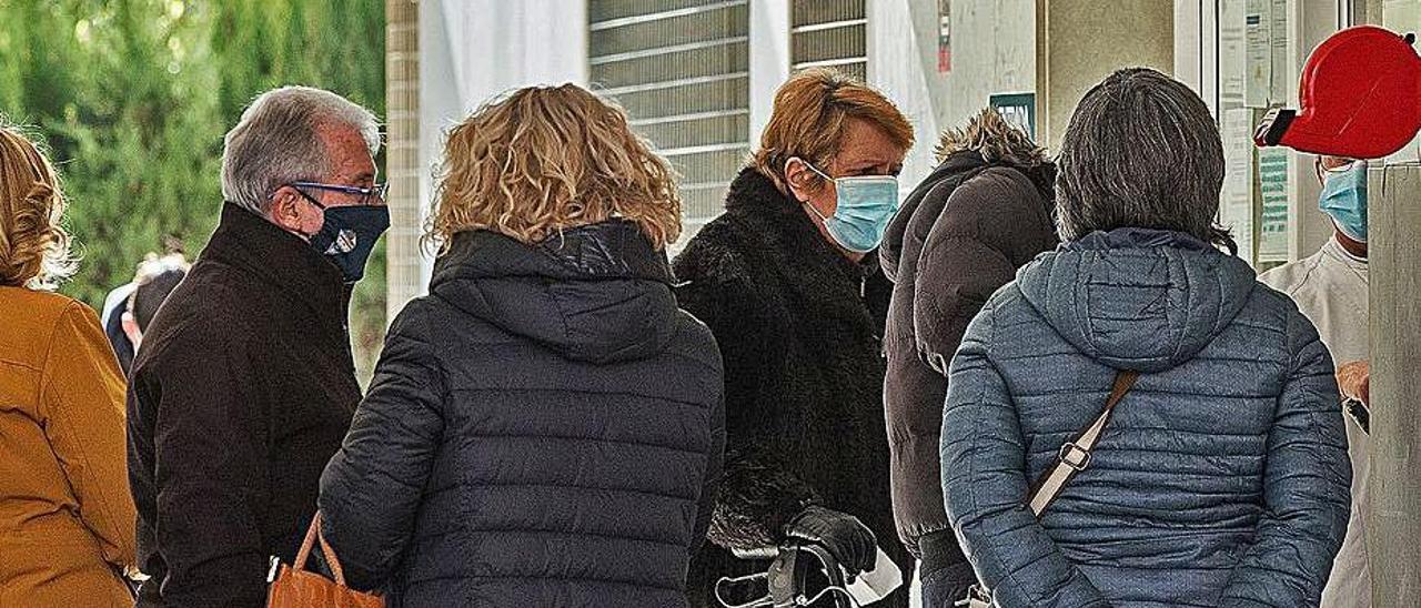 Colas de pacientes a las puertas de un centro de salud. | ALEX DOMÍNGUEZ