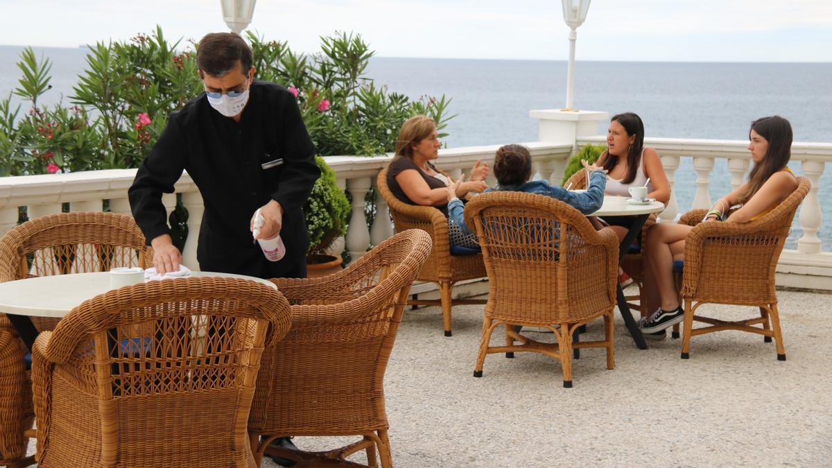 Un cambrer desinfectant les cadires de la terrassa de l'Hotel Costa Brava