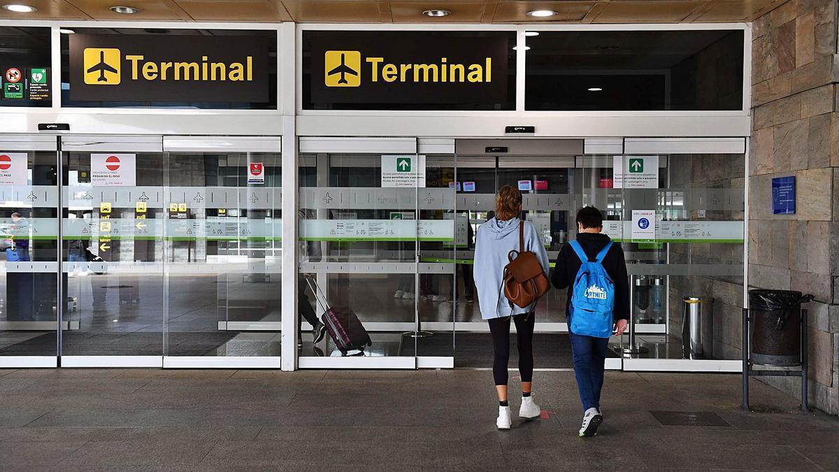 Dos personas entran en el aeropuerto de Alvedro. |   // VÍCTOR ECHAVE