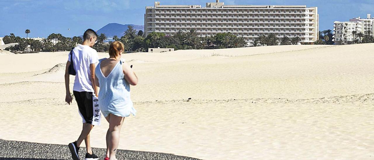 Una pareja camina por el complejo dunar de Corralejo. Al fondo, el hotel Oliva Beach.     LP/DLP