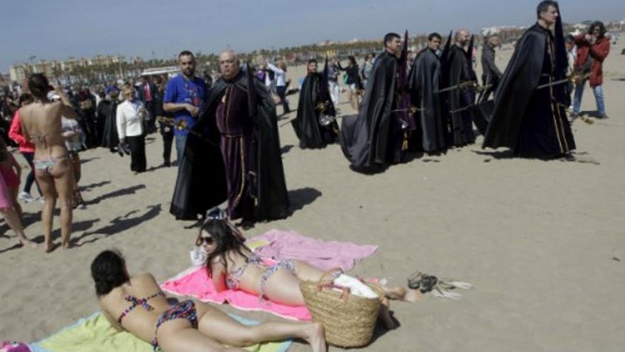 Cofrades y turistas se mezclan en la playa del Cabanyal