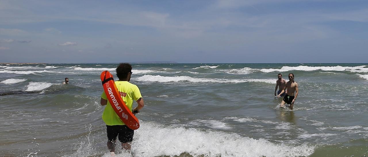 Un socorrista llama la atención a unos jóvenes en una playa