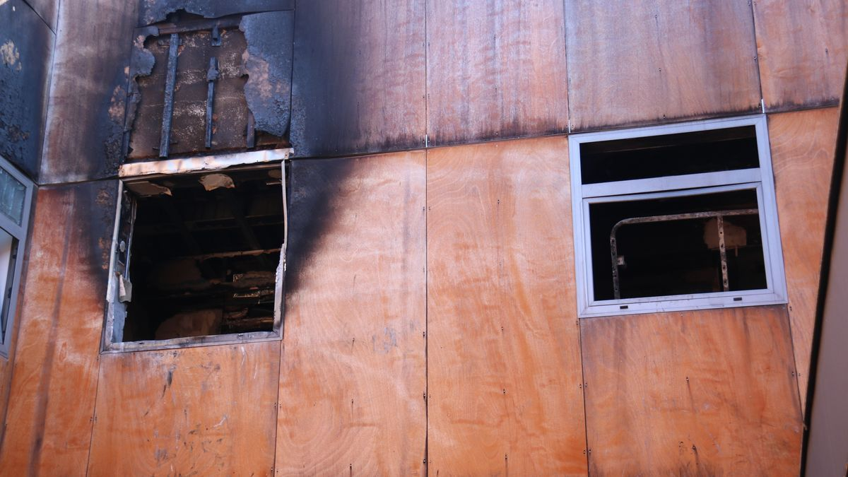 Pla detall de les dues finestres del pis de dalt de l'immoble incendiat on hi ha mort una nena al centre de Terrassa des del pati interior de la finca, el 29 de juliol de 2021. (Horitzontal)