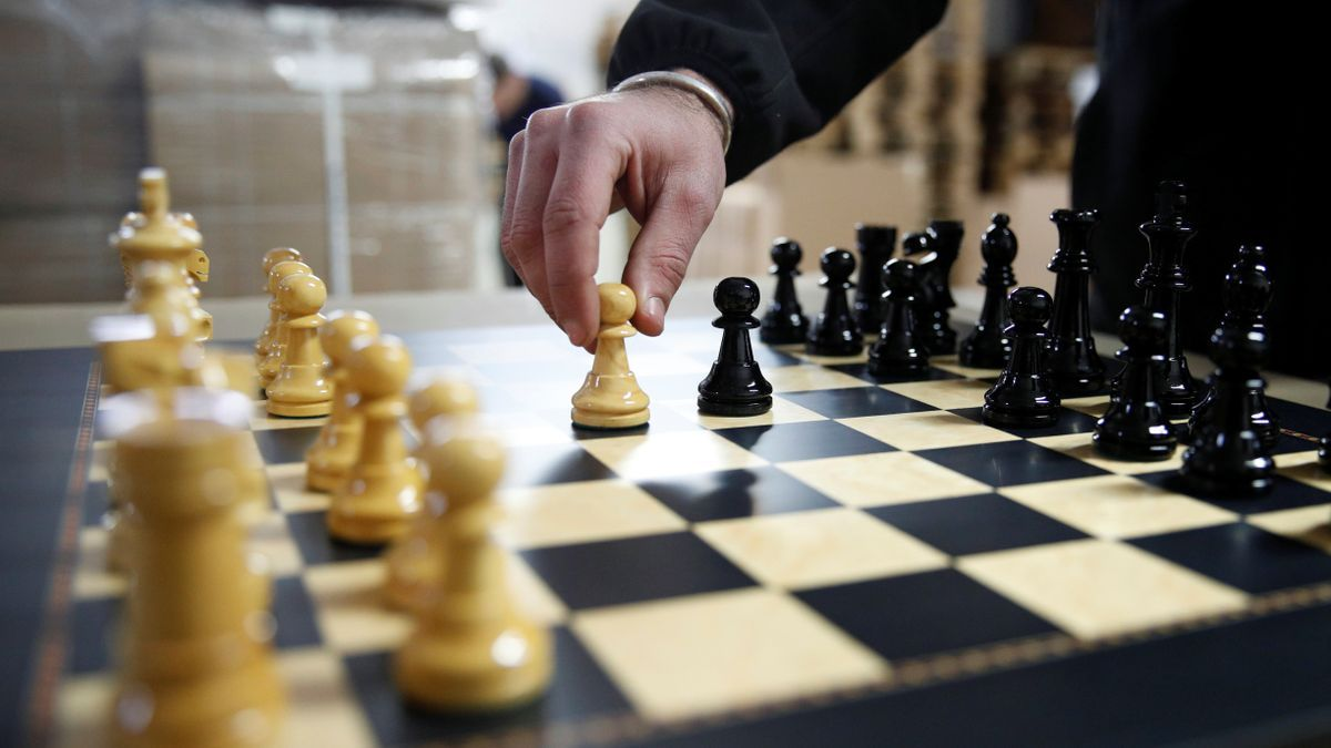 David Ferrer moves a chess pawn on a chessboard at the Rechapados Ferrer factory in La Garriga