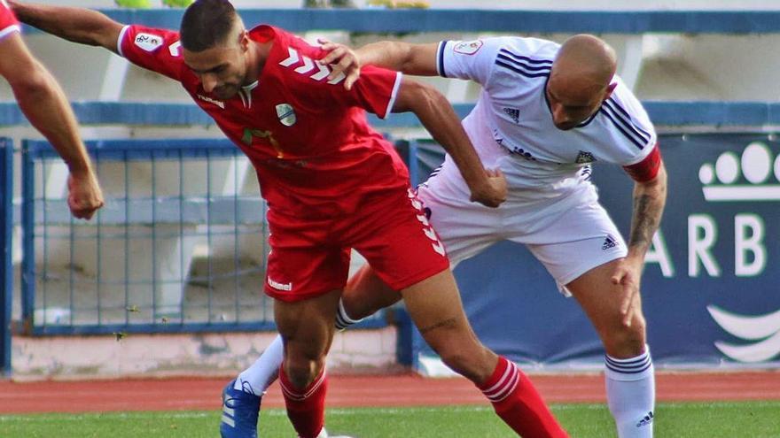 Ismael Fagir -de rojo- intenta controlar el balón ante la presión de un jugador del Marbella en el partido de ayer.
