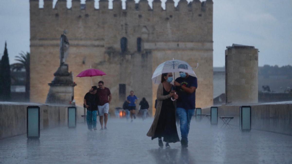 Dos parejas se cubren con paraguas en medio de una intensa lluvia en el Puente Romano.