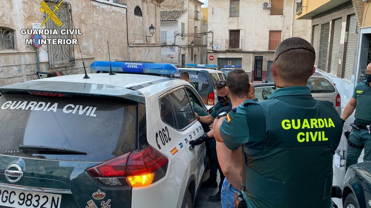 Agentes de la Guardia Civil trasladan a uno de los detenidos