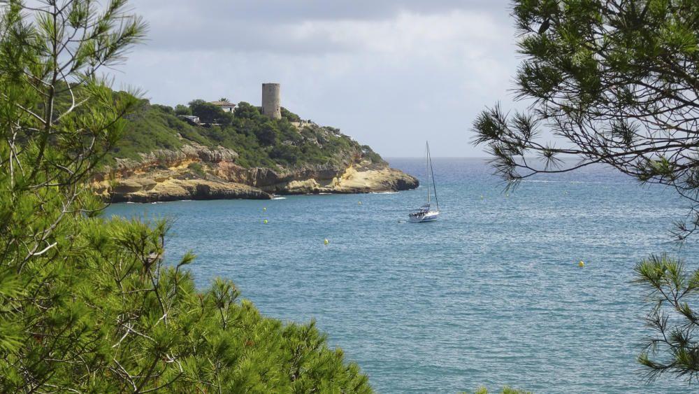 Torre de la Mora, un mar calmat, amb la torre al  fons.