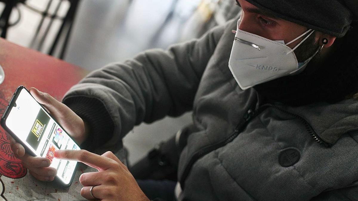 Un joven consulta ofertas en su móvil. |   // EDUARDO PARRA