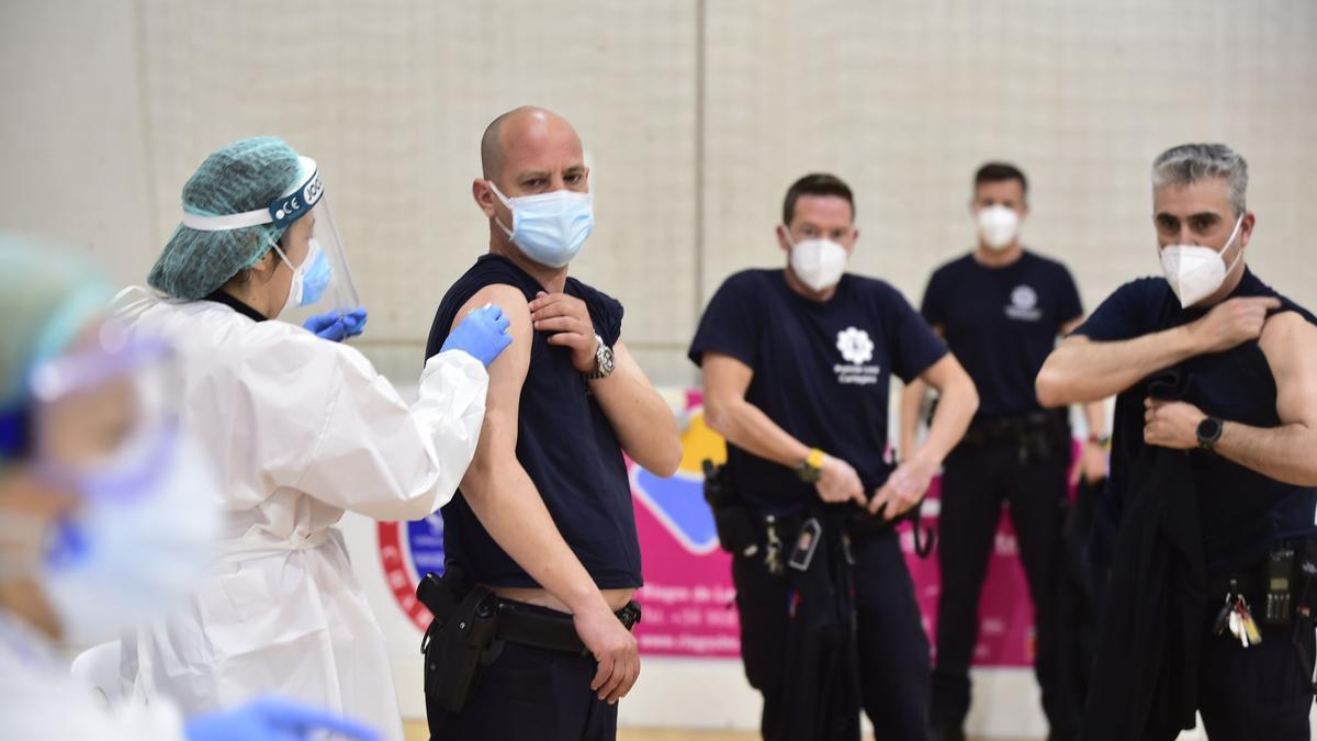 Policías de uniforme reciben la primera dosis.