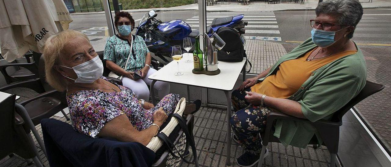 Arriba, Amelia Vinagre, Celia Vega y Ángeles Conde, ayer, en la terraza de un bar de La Corredoria.