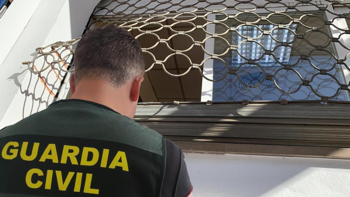 Un guardia civil junto a la verja forzada de un establecimiento desvalijado de Marratxí.
