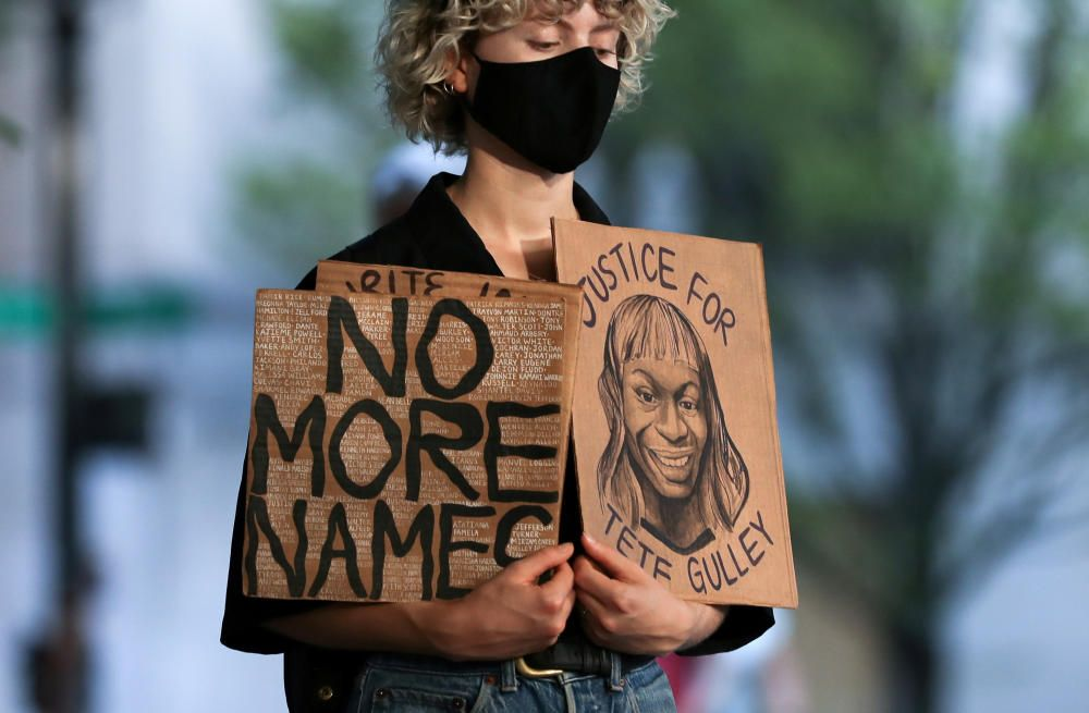 A demonstrator holds signs as she participates ...
