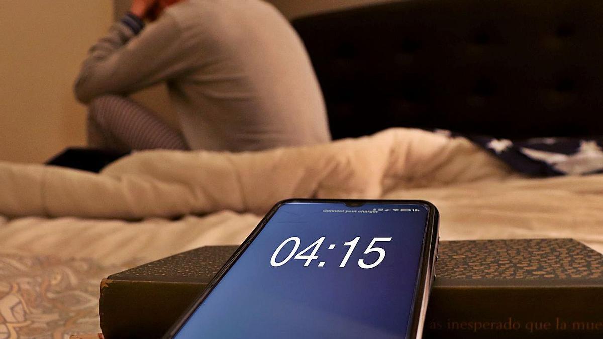 Un hombre con problemas para dormir, de madrugada, sentado en la cama.   L.O.