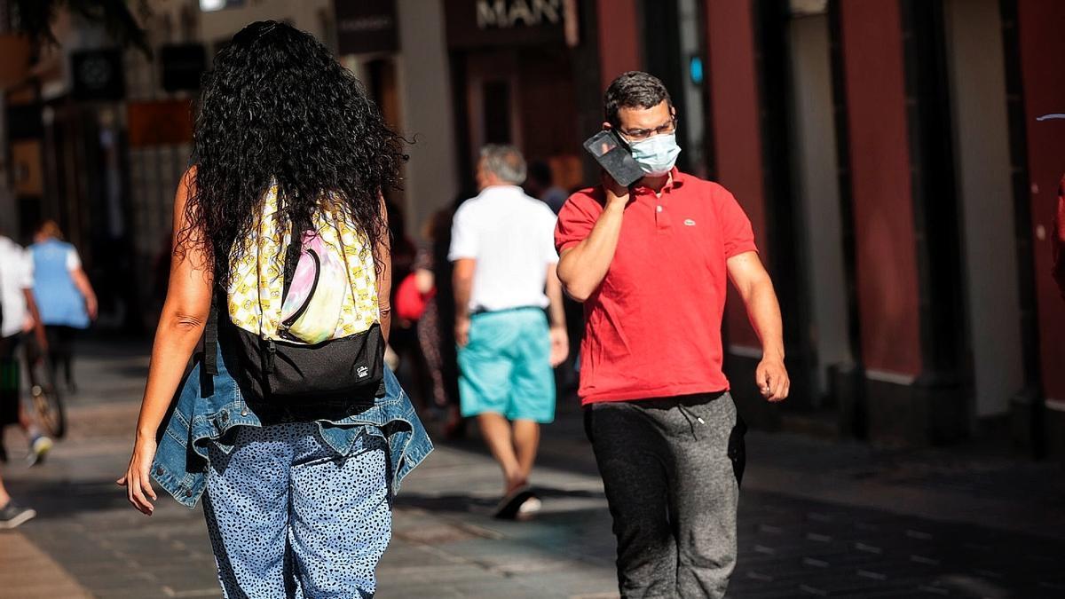 Un hombre habla por teléfono mientras camina por la calle del Castillo.