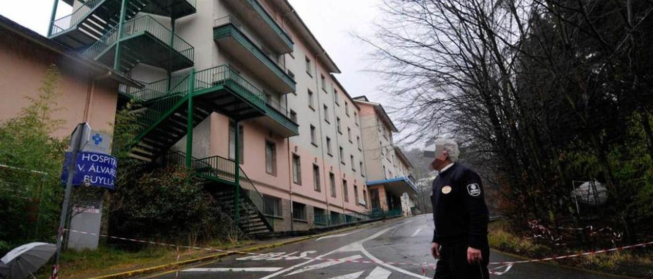 Un guardia de seguridad, ayer, ante las instalaciones del viejo hospital Álvarez Buylla de Mieres.