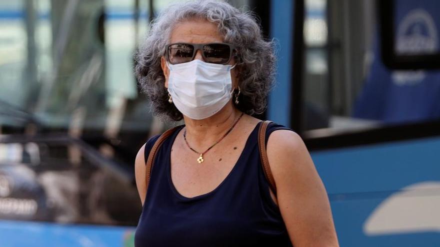 Una mujer pasea con mascarilla.